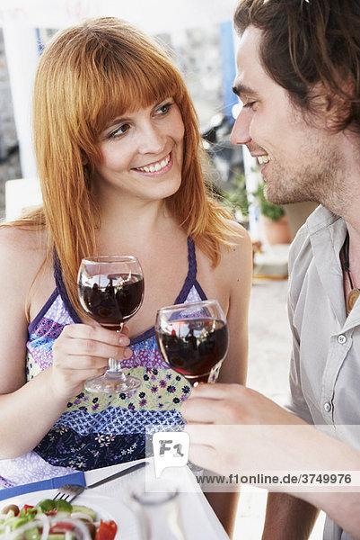 Paare chinking Gläser mit Rotwein