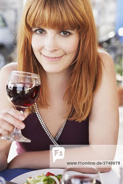 Junge Frau schlürft Rotwein