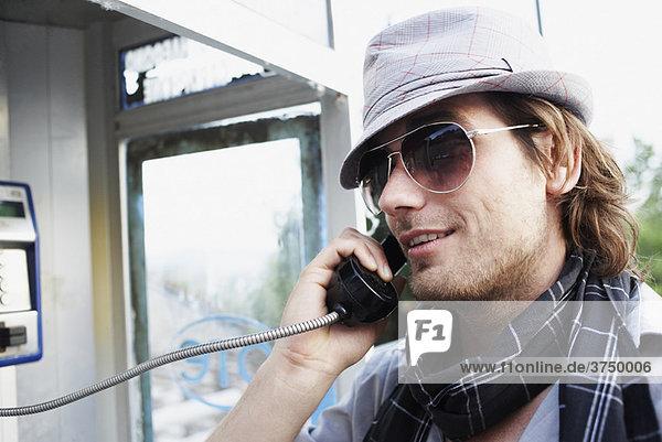 Mann spricht an der Telefonzelle