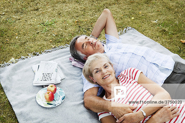 Pärchen auf Picknickdecke im Gras liegend