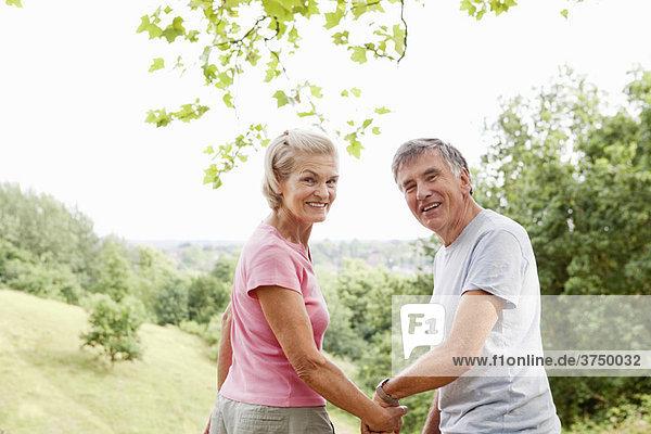 Ein reifes Paar  das sich an den Händen hält und zurückblickt.