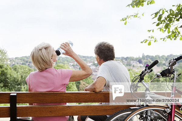 Erwachsenes Paar  das sich auf der Parkbank ausruht
