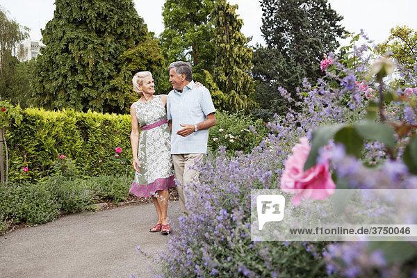 Reife Paare beim Spaziergang im Rosengarten