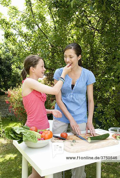Tochter füttert Mutter Salat  im Freien