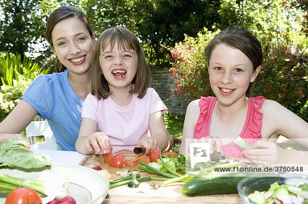 Glückliche Mutter und Töchter bereiten das Essen zu.