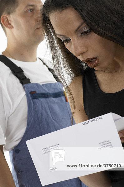 Frau kontrolliert eine Offerte  Handwerker hinten