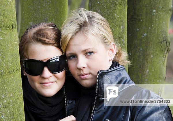 Zwei Teenies  Teenager im Alter von 15 und 16 Jahren umgeben von Baumstämmen in einem Park  Berlin  Deutschland  Europa