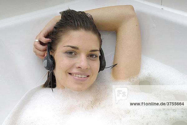 Dunkelhaarige Frau in der Badewanne hört Musik mit Kopfhörern