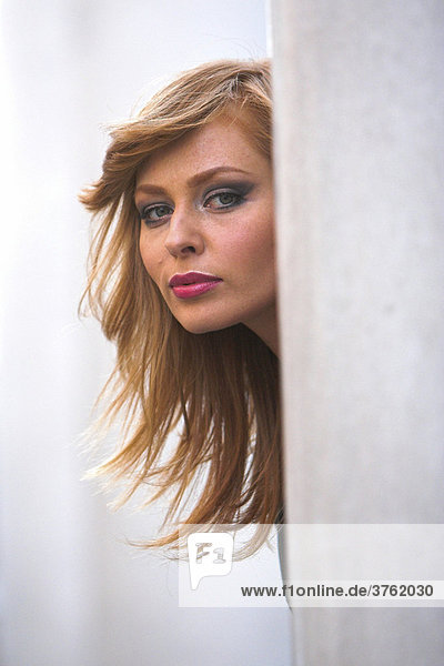 Red-haired woman looking from behind a pillar