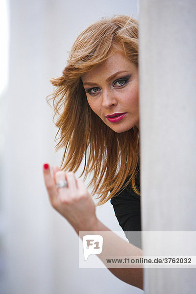 Come to me... Red-haired woman looking from behind a pillar