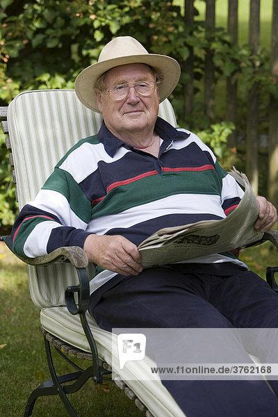 Ein Senior entspannt beim Zeitunglesen im Garten