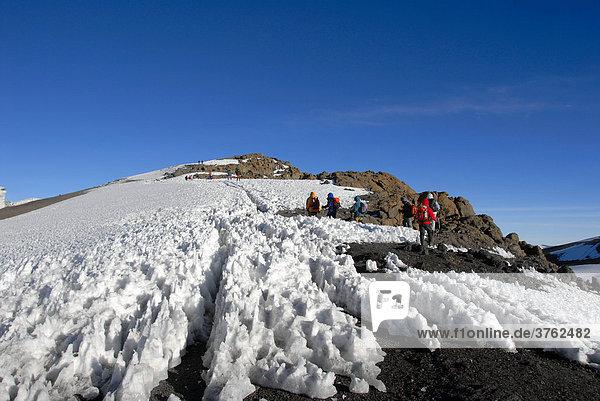 Gruppe Bergsteiger läuft durch verharschten Schnee zum Uhuru Peak Kraterrand Kilimandscharo Tansania