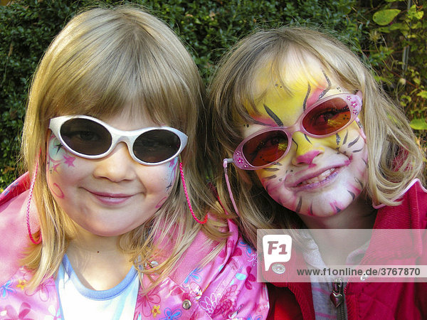 Little friends  two painted girls with sunglasses  5 years old  are smiling into the camera