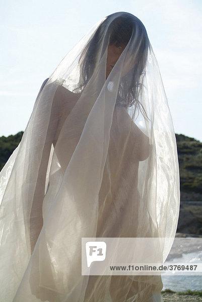 Nackte, junge Frau am Strand in ein durchsichtiges Tuch