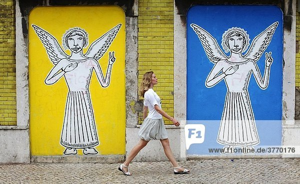 Woman walking near a wall painting with angels in Lisbon streets  Portugal  Europe