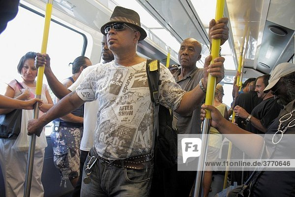 Florida  Miami  Omni Loop  Metromover  public transportation  mass transit  automated people-mover  passenger  Black  Hispanic  man  woman  standing  crowded  holding on  urban