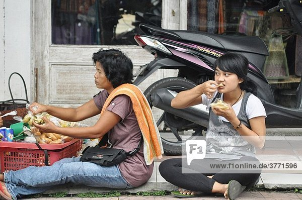 Ubud (Bali  Indonesia): a shop´s seller eating on the sidewalk  after buying a meal from a food seller