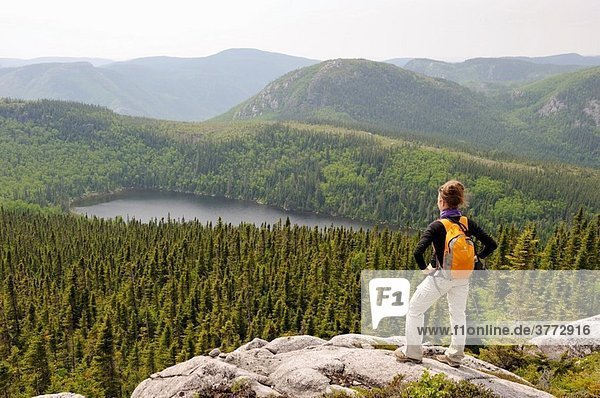 young woman admiring landscape with Pioui lake  Pioui path  Grands-Jardins National Park  Province of Quebec  Canada  North America
