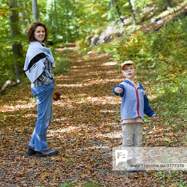 A five year old boy and his mother taking a walk in an autumnal forest