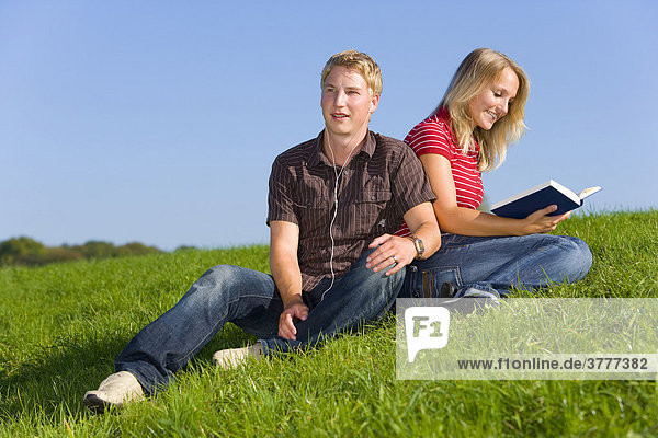 A young couple on a meadow  he is listening to music  she is reading a book