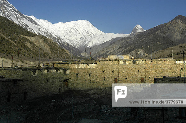 Long stone house with ice-capped mountain range Grand Barrier and Tilicho Peak in the background