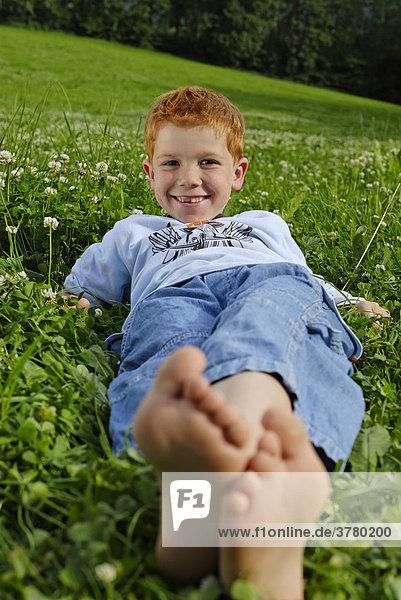 Boy lies barfoot in a meadow