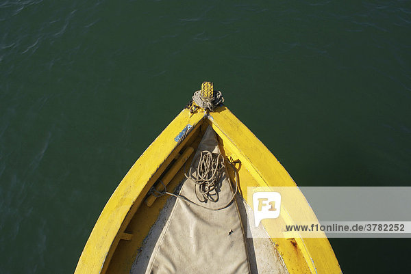Yellow bow of a fishing boat on green water