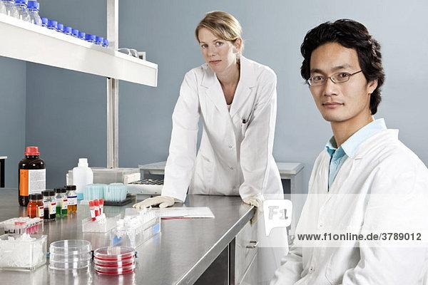 Zwei Laboranten in einem Labor mit Blick auf die Kamera