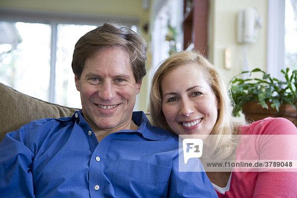 Ein lächelndes Paar sitzt auf einer Couch.