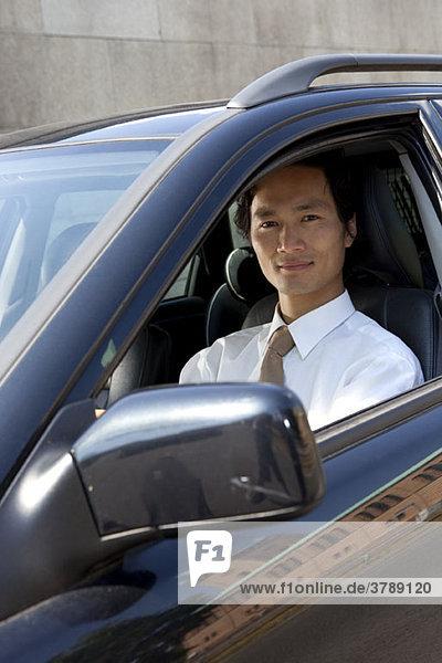 Ein Geschäftsmann in seinem Auto  der in die Kamera schaut.