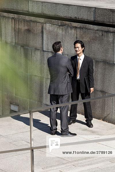 Zwei Geschäftsleute  die draußen reden.