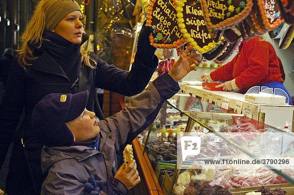 Kleiner Junge und junge Frau an einem Lebkuchenstand  Lebkuchen  Suesswaren  Weihnachtsmarkt  Weihnachten  Dortmund  NRW  Nordrhein Westfalen  Deutschland Kleiner Junge und junge Frau an einem Lebkuchenstand, Lebkuchen, Suesswaren, Weihnachtsmarkt, Weihnachten, Dortmund, NRW, Nordrhein Westfalen, Deutschland