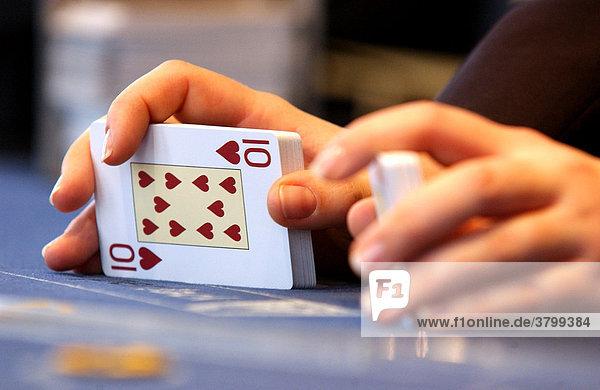 Spiel Casino im 37. Stock des Forum Hotel in Berlin Mitte. Haende beim Mischen von Karten und sortieren von Chips bei Black Jack und Roulette.
