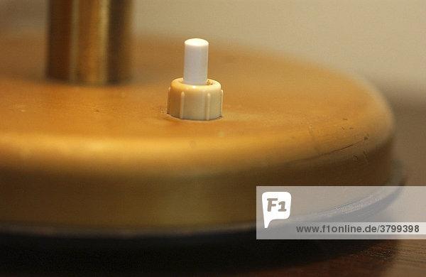 Besuch im Elterhaus: Details und Erinnerungen. Detail einer Nachttischlampe  Schalter  Tippschalter als Plastik  Plastikschalter am Lampenfuss. Besuch im Elterhaus: Details und Erinnerungen. Detail einer Nachttischlampe, Schalter, Tippschalter als Plastik, Plastikschalter am Lampenfuss.