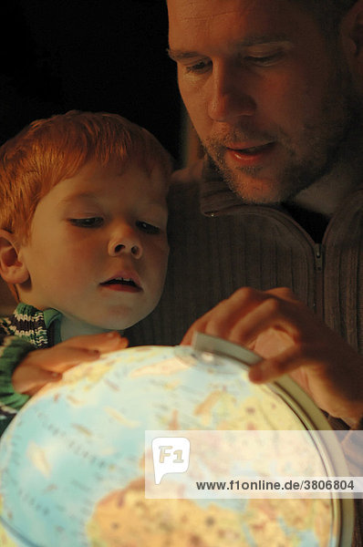 Father studies a globe with his child