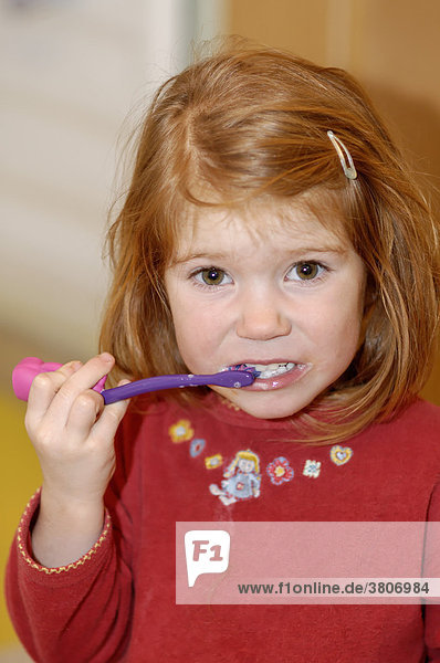 Girl 4 years old brushing her teeth