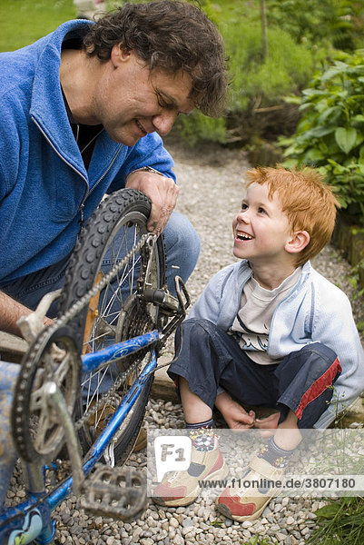 Father helps his son reparing his bicycle