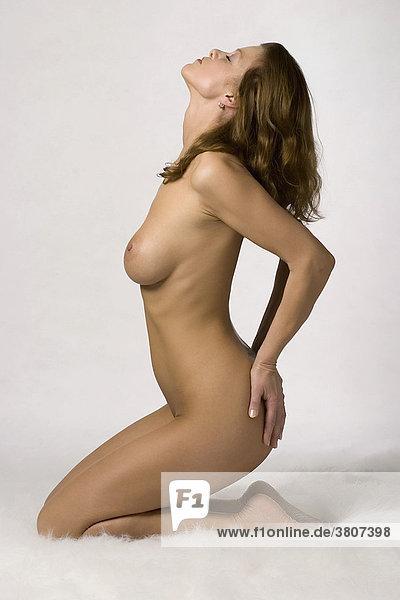 Kniender Frauen Akt in Seitenansicht