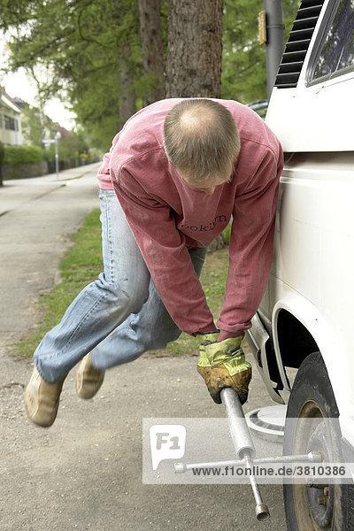 Mann versucht die Radmuttern bei einem alten VW-Bus zu lösen   Mann versucht die Radmuttern bei einem alten VW-Bus zu lösen  