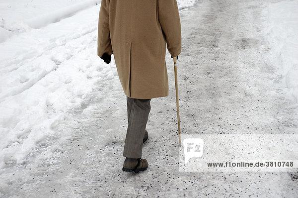 Alter Mann mit Stock läuft auf vereistem Weg