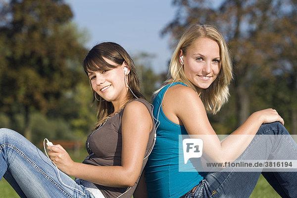 Zwei Freundinnen sitzen in einem Park und hören gemeinsam Musik