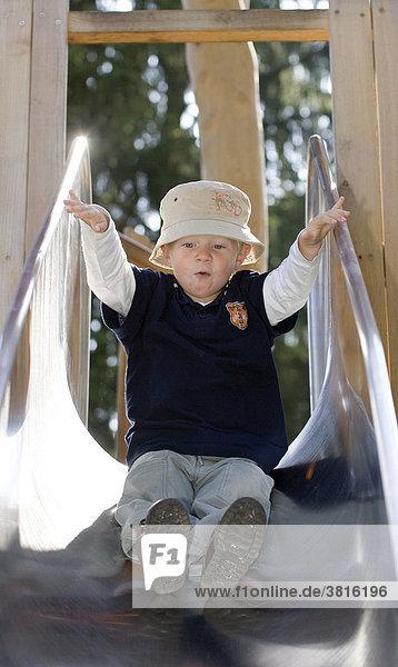 A three year old boy on a slide