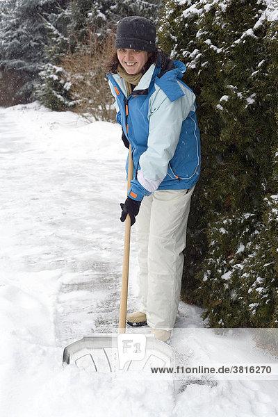 Eine Frau beim Schneeschieben - Pflicht für alle Hauseigentümer