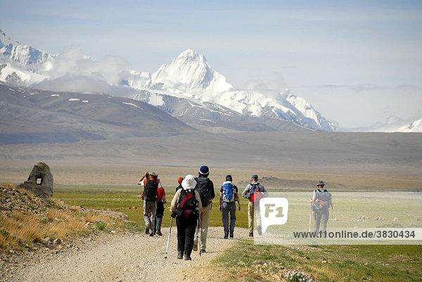 Trekking group hiking towards snow covered mountains near Old Tingri Tibet China