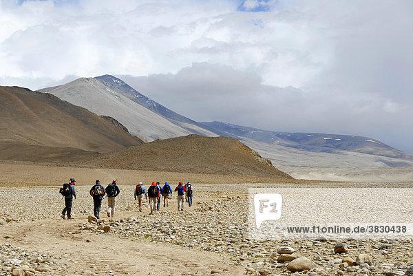 Trekkinggruppe geht über ein weites ebenes Flußtal in starkem Sturm bei Lungchang Tibet China