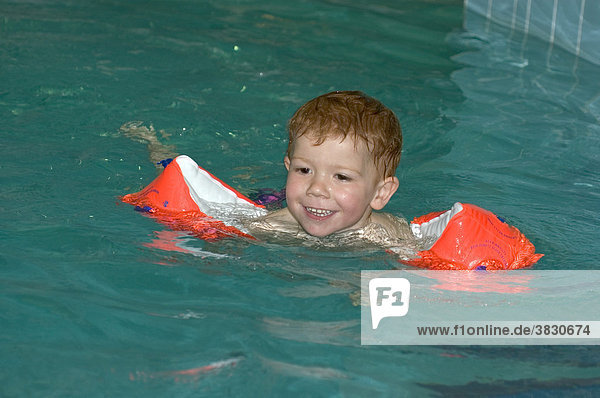 Child swims in a swimming pool