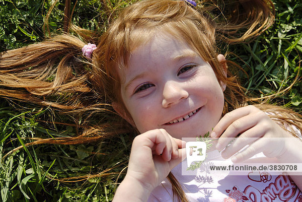 Antonia lies and plays in a meadow and is happy
