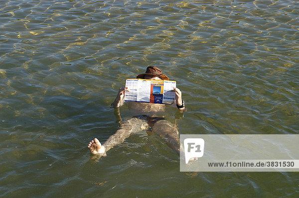 Mann liest Zeitung in einem Salzsee mit 7 facher Salzkonzentration als das Meer bei Beachport Südaustralien