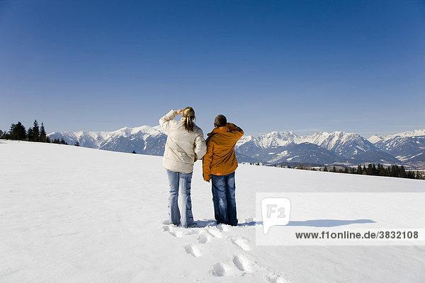 Frau mit jungem Mann in einer verschneiten Winterlandschaft
