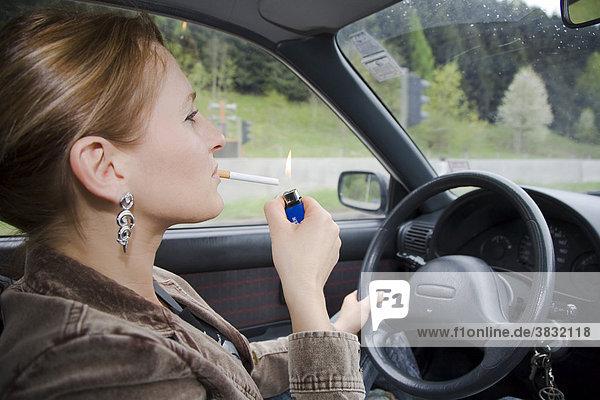 Symbolfoto - Frau raucht während dem Autofahren